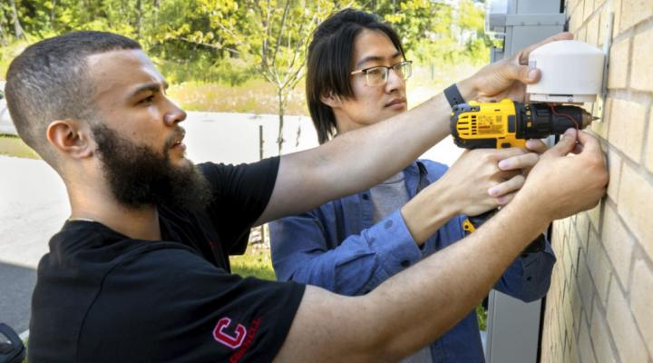 Doctoral candidate Alfredo Rodriguez, foreground, and Qingxuan Sun, a visiting Ph.D., install an Internet of Things-based outdoor air quality monitor in summer 2019.