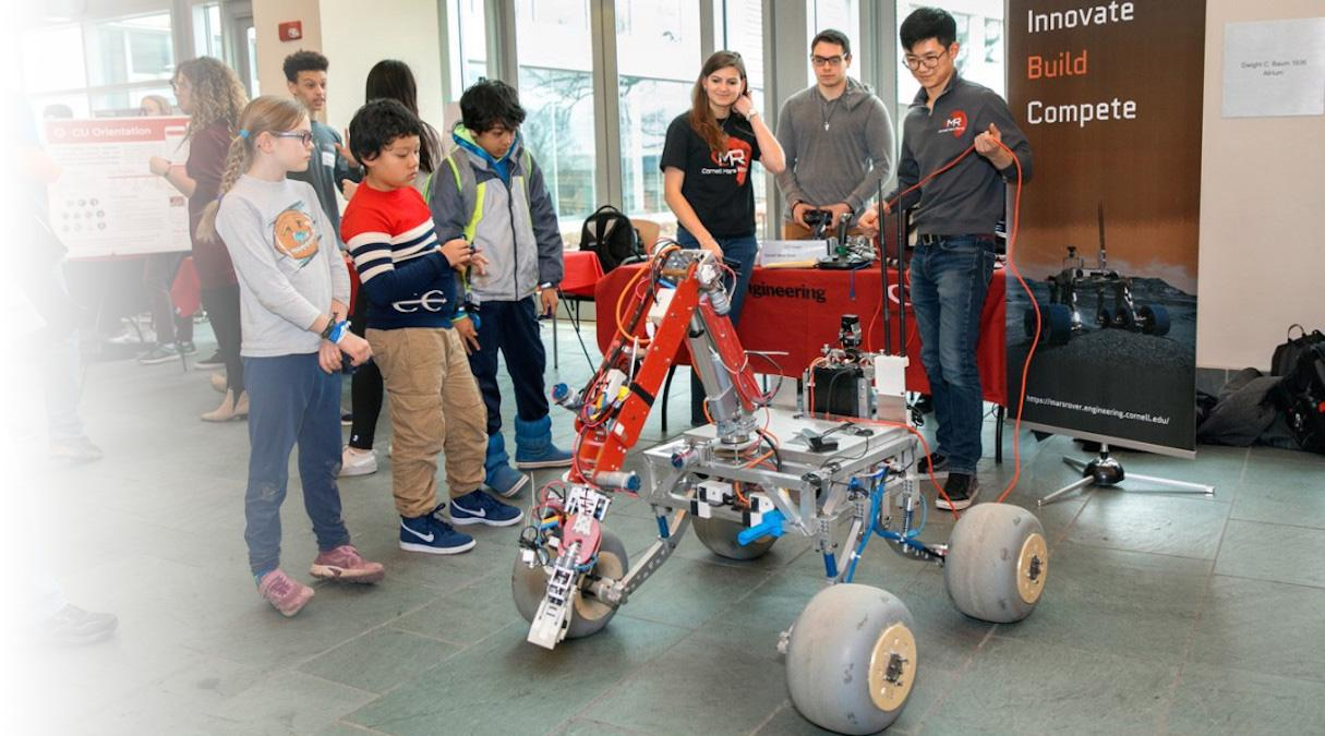 Members of the Cornell Mars Rover team operates the rover as three area young people look on during the 20th BOOM technology showcase event, April 18 in the Duffield Hall atrium.
