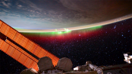 The Earth's atmosphere, featuring the aurora borealis, is pictured from the International Space Station.