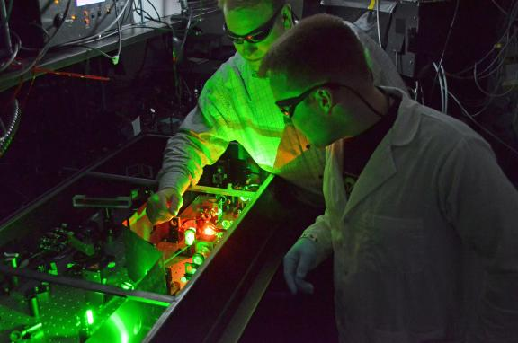 BME professor Chris Schaffer and a grad student are illuminated by green laser light in Schaffer's lab.