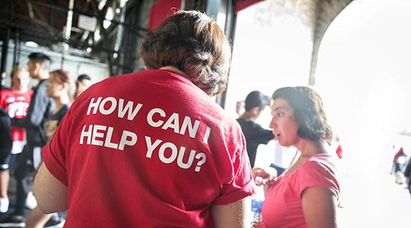 "Picture of a woman wearing a tshirt that says, ""How can I help you?"""