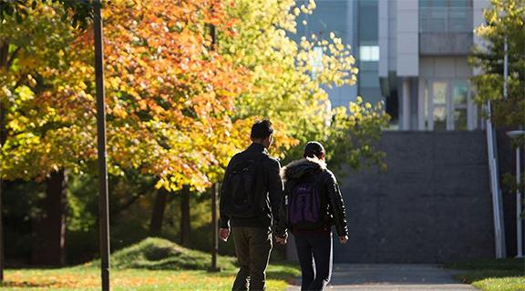 Two students walking in fall towards Duffield Hall