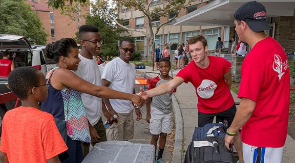 Students helping first-year student move into residence hall