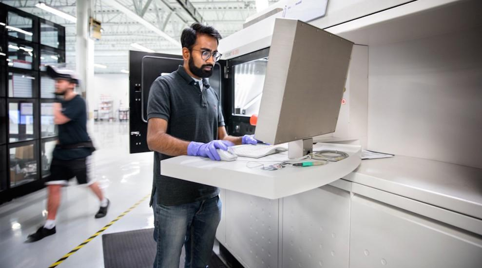 Ajay Krishnan sets up a metal 3-D printing machine for a job at Incodema3D