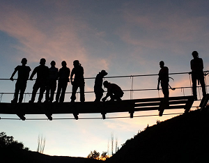 Cornell engineering students silhouetted on a bridge they have built